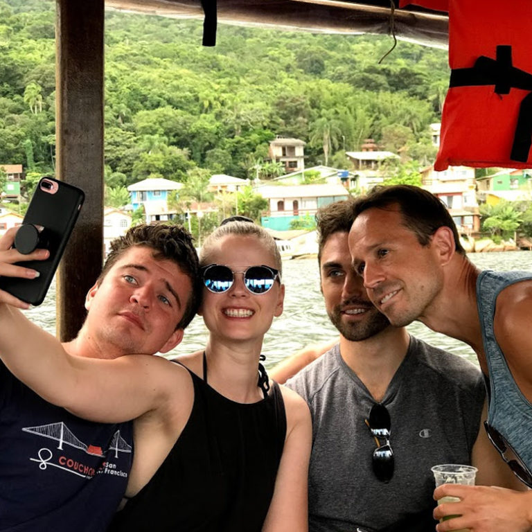 Remote worker community pose for photo on boat in Florianopolis, Brazil