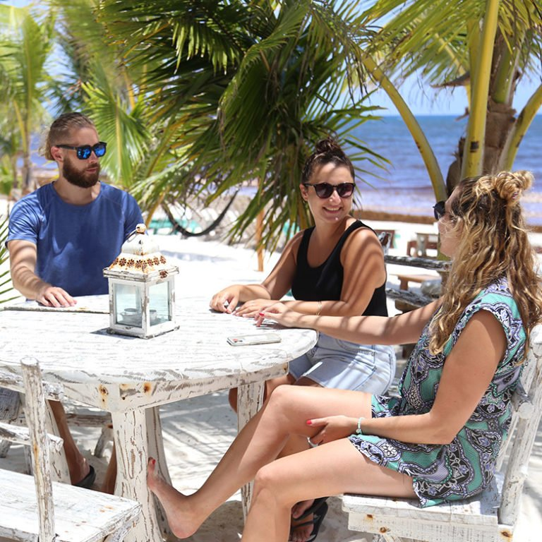 Remote workers enjoy the shade at a beach restaurant in Tulum, Mexico