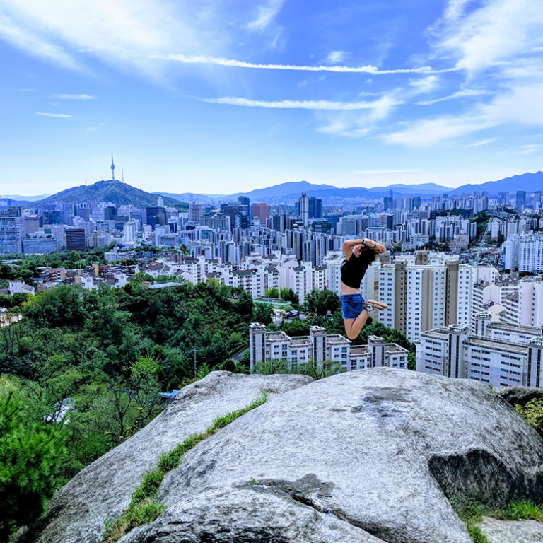 Digital nomad jumps into the air after hiking mountain in Seoul, Korea with view of Namsan Tower