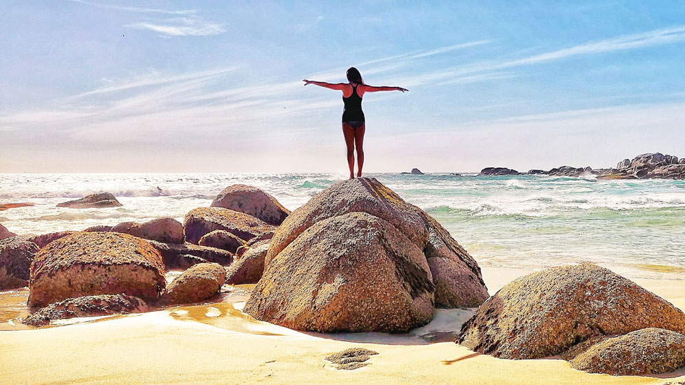 digital nomad standing on a rock staring into the ocean in cape town
