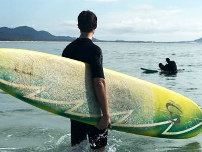 Remote worker takes morning surfing lesson in Florianopolis, Brazil