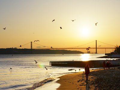 Travelers enjoying the sunrise on the peaceful beach in Lisbon, Portugal