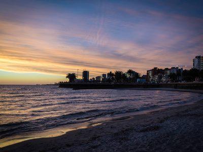 Digital nomads watch the sunset from Playa Ramirez in Montevideo, Uruguay