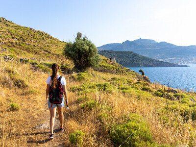 Woman walking on scenic seashore - Lesbos, Greece