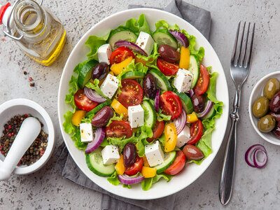 greek salad ( tomato, cucumber, bel pepper, olives  and feta cheese) in white bowl, top view